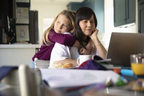 Affectionate Latinx daughter hugging mother working at laptop - HEROF19091