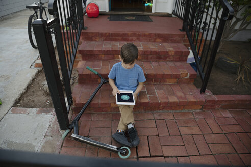Latinx boy with scooter using digital tablet on front stoop - HEROF19238