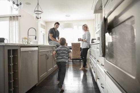 Parents watching son running in kitchen - HEROF19295