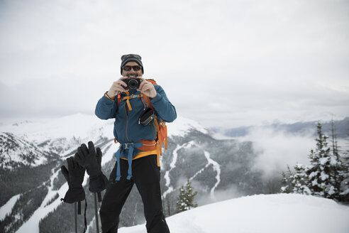 Portrait smiling man snowshoeing, using digital camera in snow with scenic mountain view - HEROF19352