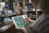 Close up female engineer examining digital circuit board on digital tablet - HEROF19377