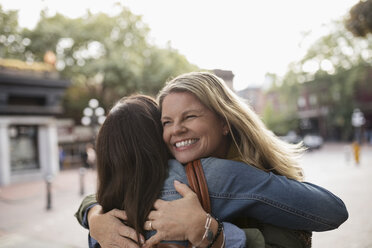Enthusiastic mature women friends hugging on urban street - HEROF19413