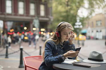 Blonde young woman with headphones listening to music with smart phone at urban sidewalk cafe - HEROF19419
