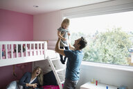 Affectionate father lifting toddler daughter in bedroom - HEROF19425