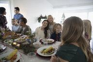 Family enjoying Christmas dinner at table - HEROF19464