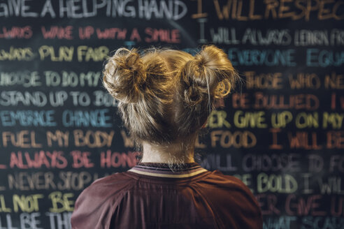 Caucasian tween blonde girl with pigtail hair bun looking at chalk text on wall - HEROF19479