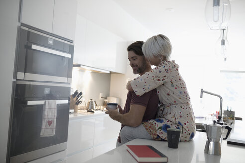 Affectionate, romantic couple hugging and drinking coffee in morning kitchen - HEROF19518