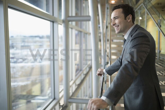 Smiling, happy Caucasian businessman looking out office window - HEROF19545