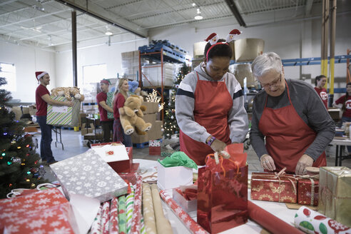 Smiling female volunteers wrapping Christmas gifts in warehouse - HEROF19557