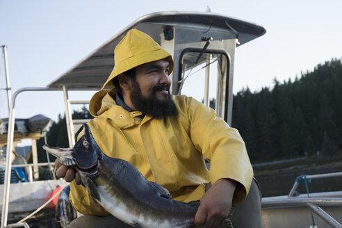 Smiling, confident fisherman holding fish on fishing boat - HEROF19584
