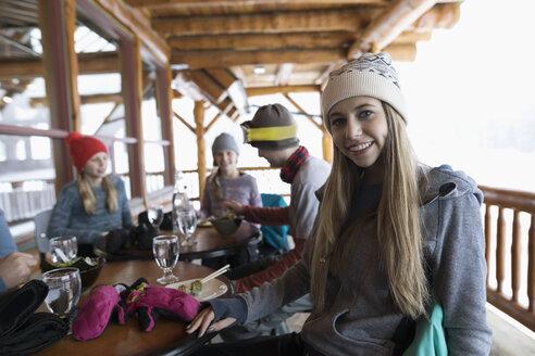 Portrait smiling, confident teenage girl skier eating with family apres-ski on ski resort lodge balcony - HEROF19668