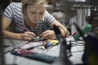 Female engineer using soldering iron on circuit board in workshop - HEROF19680