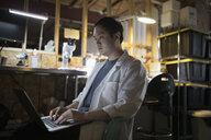 Focused male engineer working at laptop in dark workshop - HEROF19689