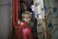 Father and toddler children hiding in tent - HEROF19728
