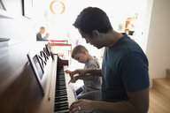 Father teaching toddler son playing piano - HEROF19731