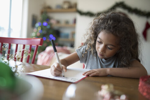 Girl writing Christmas letter to Santa at dining table - HEROF19740