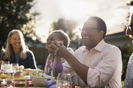 Laughing senior man enjoying garden party lunch with friends at sunny patio table - HEROF19746