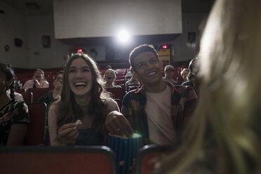 Laughing tween couple eating popcorn, watching movie in dark movie theater - HEROF19782