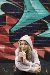 Portrait smiling young woman in hoody drinking iced coffee along graffiti wall - HEROF19854