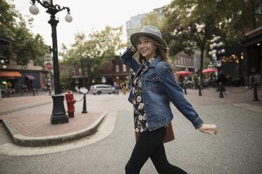 Portrait smiling, playful young woman running across urban street - HEROF19857