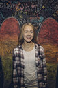 Portrait smiling, confident Caucasian tween blonde girl against wall with chalk wings - HEROF19890