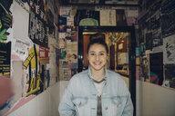 Portrait smiling, confident Caucasian tween girl in denim jacket smiling in corridor with posters - HEROF19893