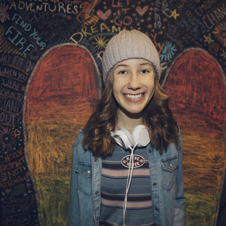 Portrait smiling, confident Caucasian tween girl with headphones against wall with chalk wings - HEROF19896