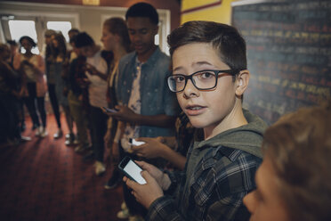 Portrait tween boy texting with smart phone, waiting in queue at movie theater - HEROF19899