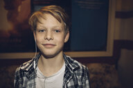 Portrait confident Caucasian blonde tween boy with headphones - HEROF19905
