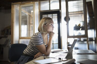 Pensive, focused woman working at laptop in office - HEROF19938