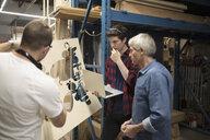 Male engineers with laptop examining laser cut wood in workshop - HEROF19953