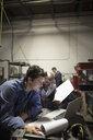 Male welders working at laptop in workshop - HEROF19956