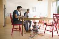 Parents working at laptops at dining table with toddler daughter playing with connector sticks on floor - HEROF19995