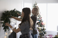 Mother and daughter decorating, hanging garland on fireplace mantle in living room - HEROF20037