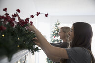 Mother and daughter decorating, hanging garland on fireplace mantle in living room - HEROF20040