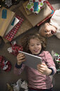 Overhead view brother and sister opening Christmas gifts, taking selfie with digital tablet - HEROF20055