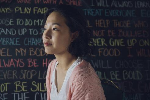 Pensive, serious Korean tween girl looking away against wall with chalk text - HEROF20058