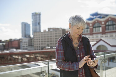 Senior woman texting with smart phone on sunny urban rooftop - HEROF20094