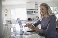 Senior woman with credit card reordering prescription medication at laptop in kitchen - HEROF20109