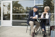 Senior couple drinking coffee and talking at sidewalk cafe - HEROF20142