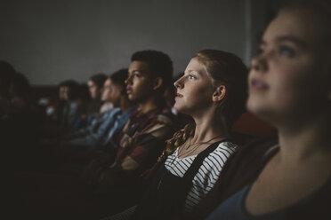 Serious tween girl watching movie in dark movie theater - HEROF20181