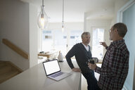 Senior male gay couple talking and drinking coffee near laptop in kitchen - HEROF20229