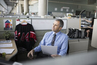 Thoughtful mature businessman reviewing paperwork in office cubicle with hockey jersey and gym bag - HEROF20253