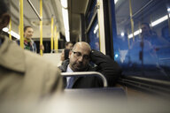Tired mature businessman commuter sleeping on bus - HEROF20262
