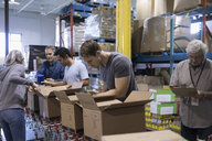 Volunteers boxing canned food for food drive in warehouse - HEROF20271
