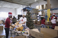 Volunteers in Santa hats organizing toys for toy drive in warehouse - HEROF20277