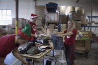 Volunteers in Santa hats sorting clothing for clothing drive in warehouse - HEROF20280