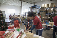 Volunteers wrapping Christmas gifts in warehouse - HEROF20289