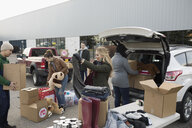 Young adult volunteers sorting and loading donations in parking lot - HEROF20298