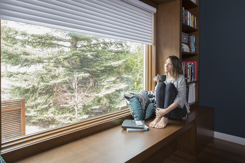 Thoughtful woman drinking coffee at window seat in home office - HEROF20328